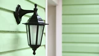CLOSE UP: In the frame there is a shot of a human hand spraying a special detergent in the form of antibacterial foam onto the decorative street lamp of a house hanging on blurred light green wall
