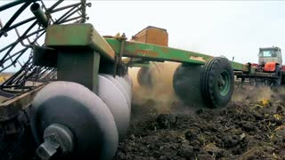 CLOSE UP, SLOW MOTION: Low angle shot of a rural tractor trailer moving across agricultural field while ploughing it preparing for sowing