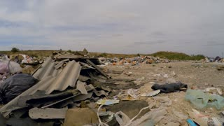 In the frame there is a moving shot over lots of garbage, wastes, trash and litter with broken slates dumped into a huge heap and packages swaying on the wind. Natural disaster captured in Ukraine