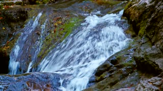 In the frame there is a picturesque shot of cascading water of mountain stream rapidly flowing down