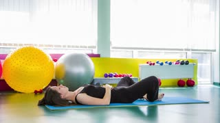 In the frame there is a side shot of young fit barefoot woman lying on the floor in final relaxation yoga pose and breathing. Bright sport equipment and large light windows on background