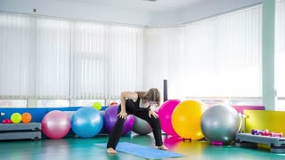 Indoor shot of a young fitness concentrated barefoot young woman changing yoga poses sitting on the mat in in gym room with lots of multicolored fitness equipment and white wall on background
