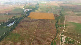 PANORAMA: Camera is moving around showing a beautiful aerial view over agricultural brown and harvest yellow fields surrounded by hills in greenery and some locality - bird's eye