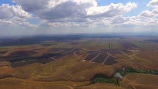 PANORAMIC: Aerial view of a beautiful scenery over several black spots of solar power stations among multi colored agricultural fields with cloudy sky on background