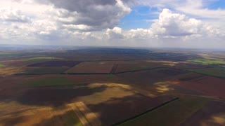 PANORAMIC: Aerial view over several black spots of solar power stations among multi colored agricultural fields with cloudy sky on background