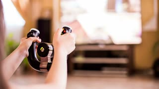 This is a closeup shot with focus on a video game console in girl's hands while she is turning it playing with it sitting on the floor.  Television set with moving images on blurred background