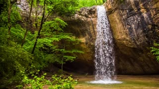 This is a scenic view of one of the most beautiful waterfall called Kozyrek (Kobalar) falling off the rock into the small lake making a water wall surrounded with green trees and bushes moving by