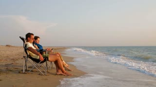 This is a side shot of a young romantic couple in light summer clothes sitting in loungers on the sandy beach enjoying the waves breaking against the seashore near their feet. Shot is made in Crimea