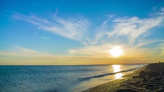 This is a tranquil scenery - relaxing background of beautiful sunset with cloudy sky above the Black sea beach with the sun and waves splashing against the seashore, Crimea