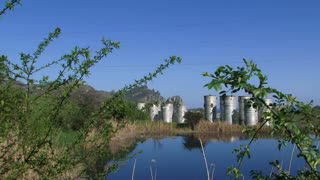 Treatment facilities situated near the lake with beautiful nature - green plants and blue sky on background