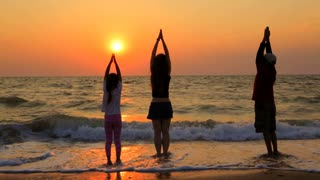 Video shot of  three children - two girls and one boy in summer clothes doing relaxation exercises on the sandy beach at beautiful sunset. At the end they do a bow and go away. The sun is shining
