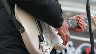 A man plays on electric guitar strings with a white body using a mediator. Slow motion.