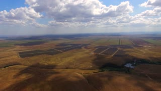 Camera is slowly moving upwards showing a very picturesque aerial view over agricultural fields of different colors with several black spots of solar power stations with cloudy sky on background