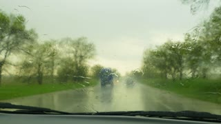 During the rain the car moves along the road. At the meeting, the cars with the headlights on are moving. Windshield wipers remove water from the windshield.