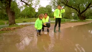 Mom allows a child dressed in rubber boots to go into a puddle, after the rain.