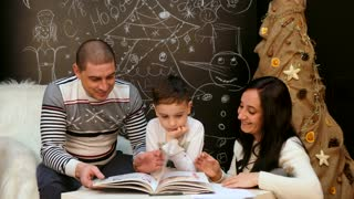 Parents read a book to their child. The family is sitting in a room with Christmas decorations. The Christmas tree is made of burlap and adorned with dried oranges