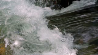 The water of a fast mountain stream forms foam on a section of a river with a small threshold