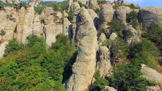 This is an aerial flying shot of rocky formations on slopes of mountain overgrown with green trees - accumulation of bizarre rock on the western slope of the southern ridge of the array Demerdzhi
