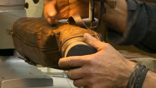A cobbler in a Shoe Repair shop uses a sewing machine to stitch together a woman's boot.