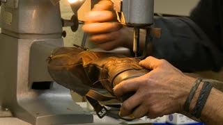 A cobbler's work in a Shoe Repair shop. He is using a sewing Machine to Stitch a woman's Boot together.