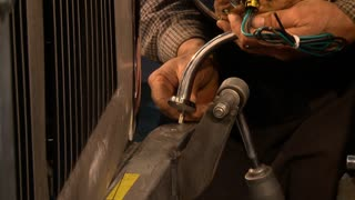 A custom metal craftsman installs a headlight mount to a hot rod frame in his shop.