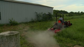 A farmer in the midwest uses a small farm tractor to mow his hay field on a cloudy summer day.
