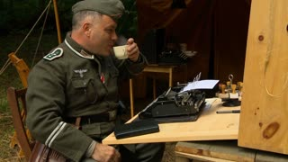 A German army communications officer sips coffee while typing his morning reports in a camp in World War II.