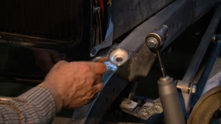 A hot rod headlight is mounted to the steel frame by a custom metal craftsman in his shop.
