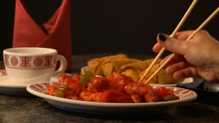 A woman uses chopsticks in a Chinese restaurant to pick up pieces of delicious traditional Asian cuisine. Spicy red chicken, egg rolls, tea and a napkin complete the scene. Shot with a black background.