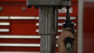 A worker uses a pneumatic wrench to assemble an industrial implement in a workshop.