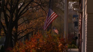 An American Flag waves in the breeze in Autumn in a Neighborhood.