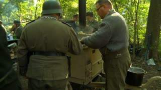 An army cook serves a steamy breakfast to soldiers from an authentic WWII German Field Kitchen in a forest camp.