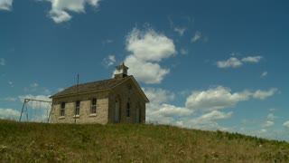 An Old One-Room Stone School on a hillside in the Kansas Flint Hills Prairie in Time lapse.