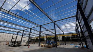 Construction of an industrial facility. Low angle pan of steel beams and equipment in the structure of a new building.