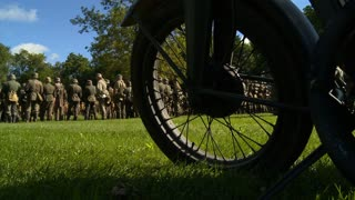 German soldiers of World War II in formation for information and inspection as seen through a motorcycle wheel.