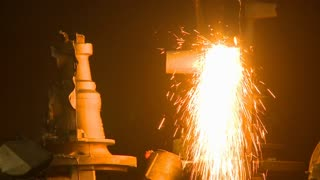 Industrial sparks with cutting torch. Sparks fly in a magnificent shower of molten steel as a helmeted factory worker creates product in an industrial plant. Safety is top concern in this hazardous environment.