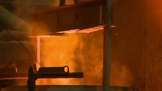 Molten steel in a large heated vat is lowered to a mold by skilled workers in a foundry. One worker uses a flaming torch. He wears protective safety equipment as this is a very dangerous environment.