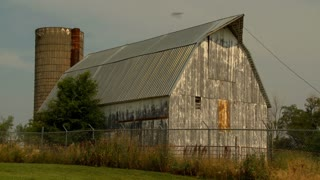 Old Barn and Silo in Kansas with chain link security fence.