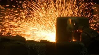 Sparks fly in a magnificent shower of molten steel as a helmeted factory worker creates product in an industrial plant.