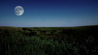 The full moon rises above a hilly prairie landscape on a summer evening. Great establishing shot of the American Midwest, the great plains and the agricultural Heartland.