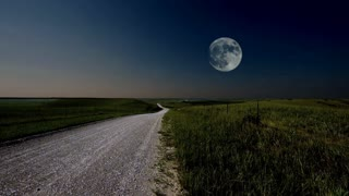 The full moon rises above a prairie landscape on a summer evening. A gravel road trails off into the horizon. Great establishing shot of the American Midwest, the great plains and the agricultural Heartland.