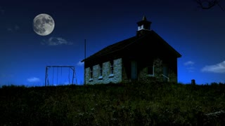The full moon rises above a stone school house and prairie landscape on a summer evening. A swing set is visible on the horizon. Great establishing shot of the American Midwest, the great plains and the American education traditions.