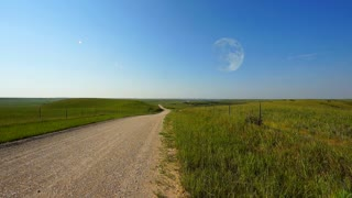 The full moon rises early above a prairie landscape on a summer afternoon. A gravel road trails off into the horizon. Great establishing shot of the American Midwest, the great plains and the agricultural Heartland.
