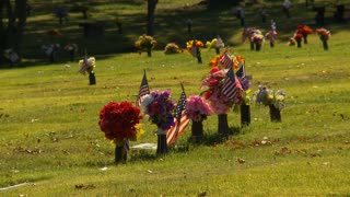 A group Veteran's Graves with American Flags and Flowers to honor their service and sacrifice.