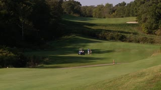 A long shot of a group of men playing golf.