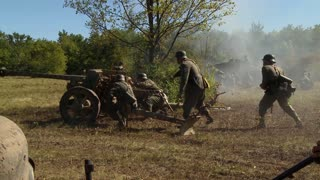 A World War II German cannon crew in combat fires with a powerful blast of smoke and flame. A tank and other troops move forward as the battle rages. They reload and fire again.
