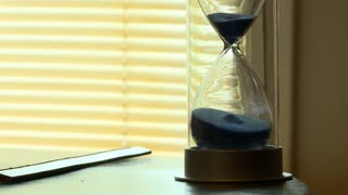An hourglass with blue sand is set on a wooden table top with an old ruler near a window with the blinds down. The sands slowly fill the bottom, marking the passage of time.