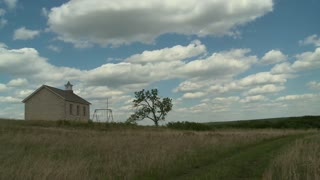 An old stone schoolhouse stands high on the Kansas prairie in this time lapsed establishing shot. An old swing-set rusts away in the weather.