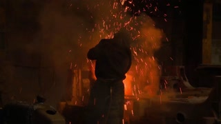 Dangerous industrial skilled labor jobs. Sparks fly in a magnificent shower of molten steel as a helmeted factory worker creates product in an industrial plant.