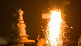 Sparks fly in a magnificent shower of molten steel as a helmeted factory worker cuts pats of the product in an industrial plant.